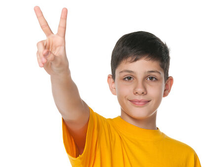 A smiling preteen boy shows victory sign against the white background photo