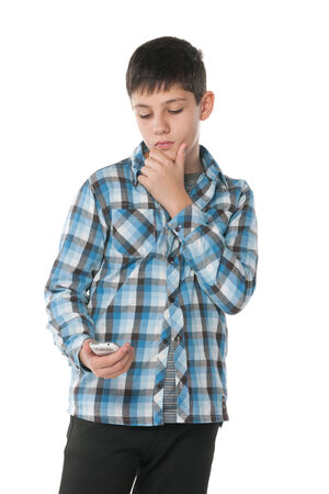 A portrait of a pensive teen with a cell phone on the white background photo