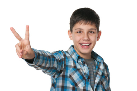 A smiling teen boy shows victory sign against the white background photo