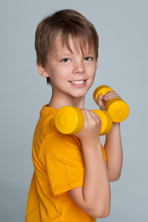 A cute young boy do exercises with dumbbells on the gray background Stock Photo