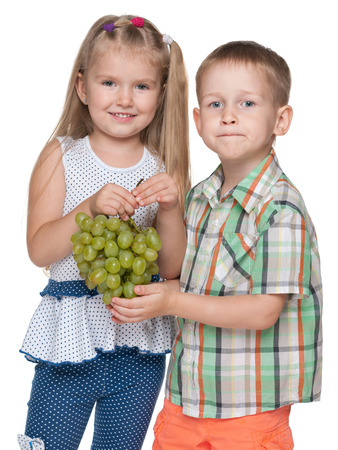 mouthful: Children hold grapes on the white background