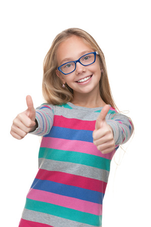 pretty preteen: A preteen girl in a glasses holds her thumbs up against the white background Stock Photo