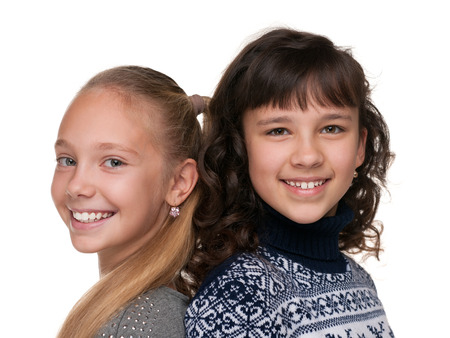 pretty preteen: Two happy girls are standing together against the white background