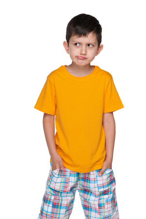 alone boy: A portrait of a very thoughtful little boy in a yellow shirt on the white