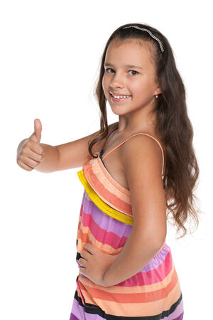 beautiful preteen girl: A smiling preteen girl holds her thumb up against the white