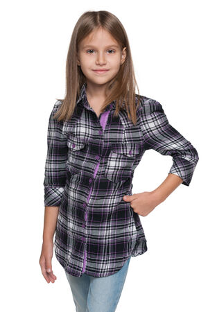A fashion young girl is standing on the white  photo