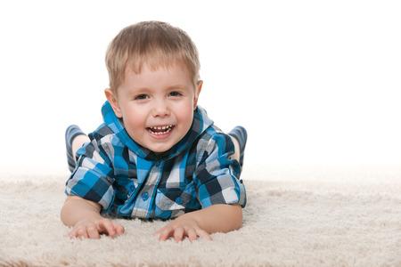 carpet: Laughing preschool boy is lying on the white carpet