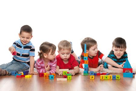Cinq enfants intelligents jouent sur le plancher à l'école maternelle