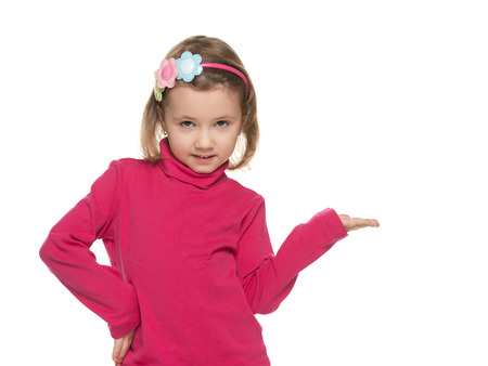A smiling little girl makes a hand gesture against the white background photo