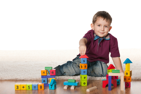 toy blocks: A little boy plays with toys on the white carpet Stock Photo