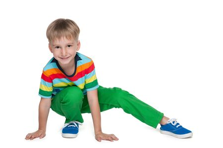 blond boy: A little blond boy in a striped shirt is sitting on the white background Stock Photo