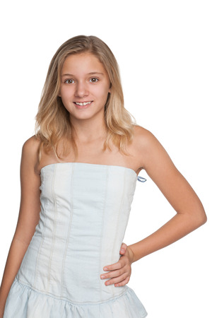 preteens girl: A blonde young girl stands against the white background