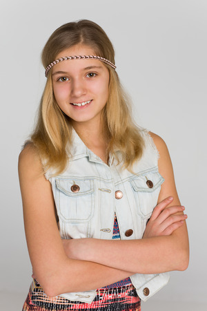 A portrait of an adorable blonde teen girl on the gray background Banque d'images