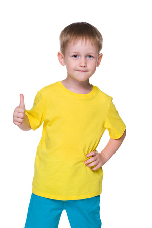 yellow shirt: A smiling little boy holds his thumb up on the white background