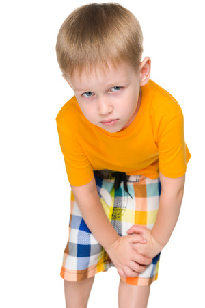 plaintive: An upset little boy stands on the white background