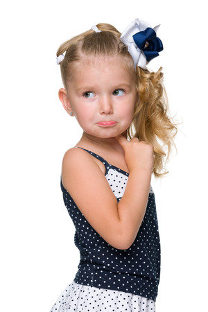 perplexity: A puzzled little girl looks back against the white background Stock Photo