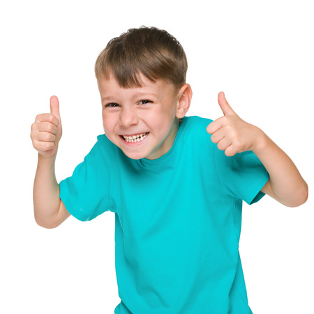 A laughing little boy holds his thumbs up against the white background