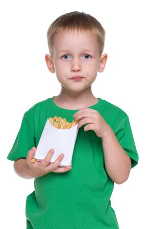 mouthful: A cute little boy eats fries on the white background