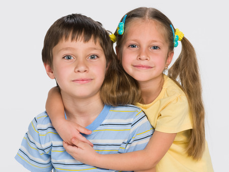 brothers and sisters: A closeup portrait of two little children together on the gray background Stock Photo