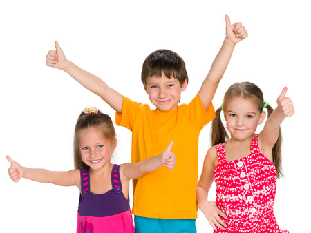 happy kids: Three cheerful children holding their thumbs up on the white background