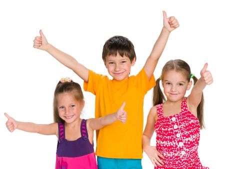 niños felices: Tres niños alegres sosteniendo sus pulgares para arriba en el fondo blanco
