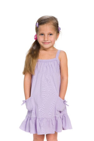 little girl dress: A cute little girl stands against the white background Stock Photo
