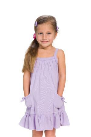petite fille avec robe: Une petite fille se dresse contre le fond blanc Banque d'images