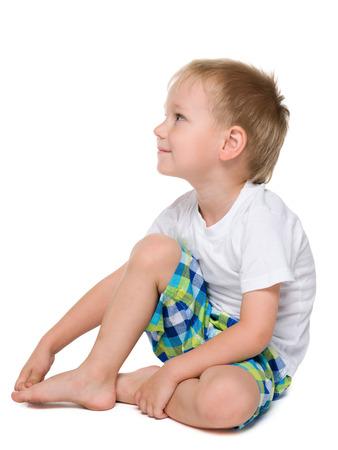 niños sentados: Un retrato de perfil de un niño pensativo se sienta en el fondo blanco