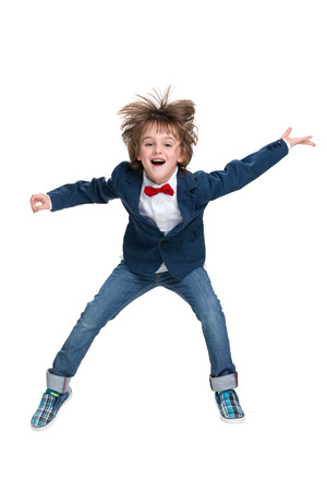 niño saltando: Un niño feliz salta en el fondo blanco