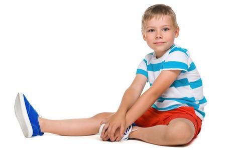 niños sentados: Un retrato de perfil de un niño pequeño lindo sobre el fondo blanco