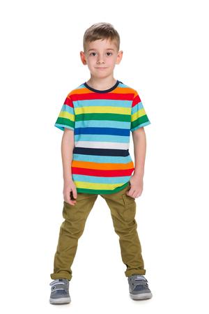 Een mode jongetje staat tegen de witte achtergrond