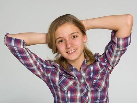 ni�os rubios: Un retrato de una ni�a adorable adolescente en el fondo gris Foto de archivo