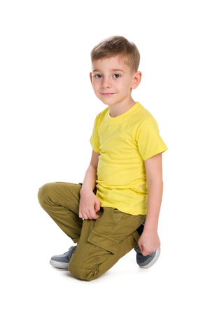 A cute little boy sits against the white background