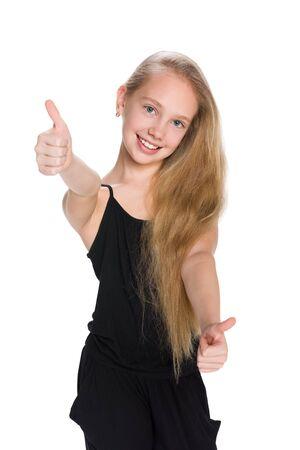 ni�os rubios: Una ni�a preadolescente riendo sostiene su pulgar hacia arriba contra el fondo blanco Foto de archivo
