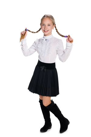 A pretty schoolgirl with pigtails stands against the white background