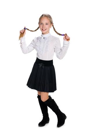 zapatos escolares: Una hermosa colegiala con trenzas se destaca contra el fondo blanco Foto de archivo