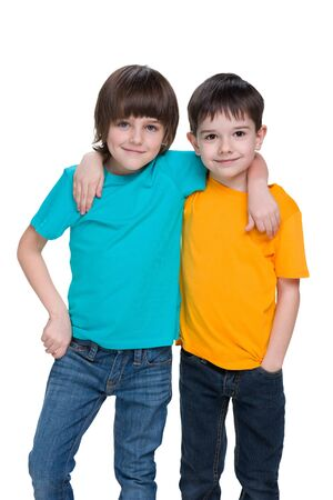 young boys: Two happy fashion young boys are standing together against the white background