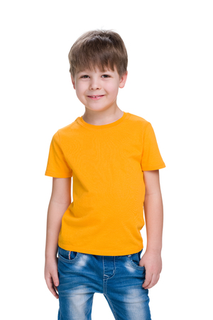 europeans: A smiling little boy in a yellow shirt stands against the white background Stock Photo