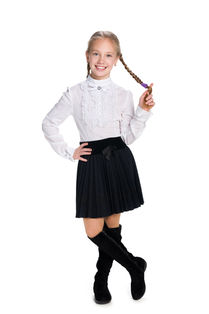A smiling schoolgirl with pigtails stands against the white background Stock Photo