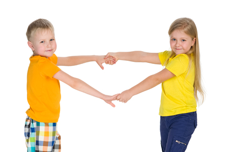 child couple: Two children hold hands against the white background