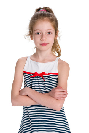 A serious young girl is standing on the white background