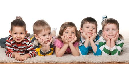 Groep van vijf kinderen op de vloer liggen op het witte tapijt