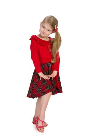 niñas pequeñas: Una niña preciosa que está de pie contra el fondo blanco Foto de archivo