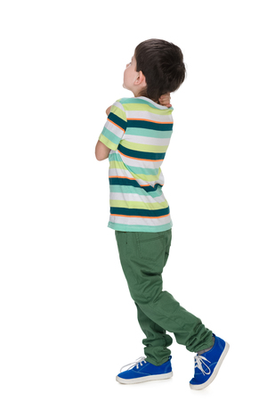 A little boy in a striped shirt looks back against the white background
