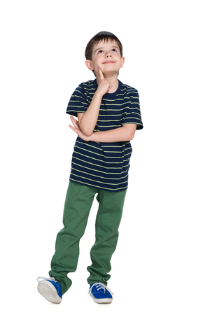 A cute little boy in a striped shirt looks up against the white background
