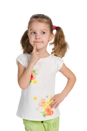 A curious little girl stands against the white background and thinks