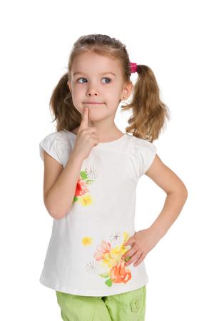 Une petite fille curieuse se dresse contre le fond blanc et pense
