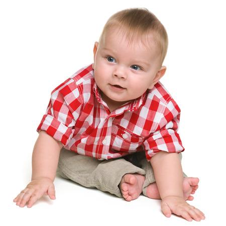 bebe sentado: Un muchacho lindo bebé está sentado en el fondo blanco Foto de archivo