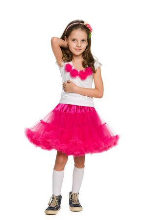 standing against: A pretty little girl is standing against the white background Stock Photo