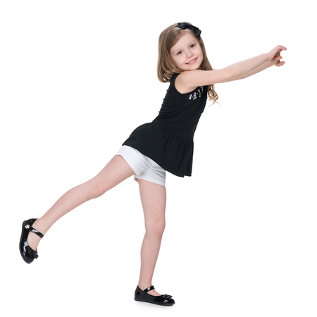 A happy little girl dances on the white background